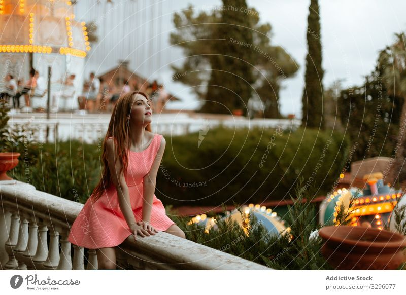 Young woman in pink dress sitting on fence in amusement park funfair romantic sensual carousel teenager fashion entertainment style trendy millennial relax