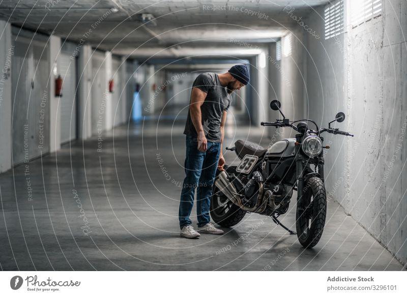 Bearded biker in garage hallway motorcycle man modern standing confident bearded transport ride male vehicle motorbike city urban corridor contemporary facility