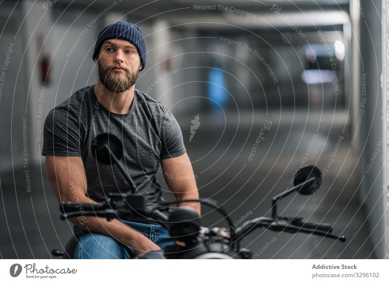 Bearded biker in garage hallway motorcycle man modern sit confident bearded transport ride male vehicle motorbike city urban corridor contemporary facility