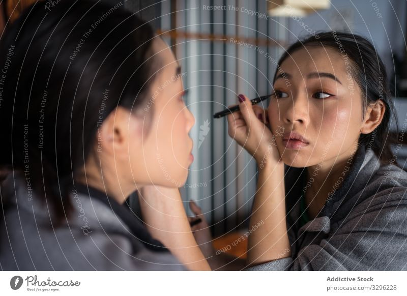 Asian woman applying eyeliner in front of mirror makeup cosmetic casual beauty eyes reflection young female face fashion care complexion facial cosmetology
