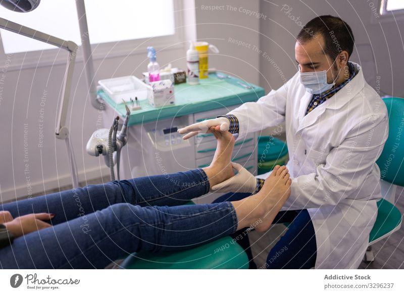 Podiatrist examining and treating patient doctor foot podiatry massage podiatrist clinic treatment procedure hospital healthcare medicine professional man