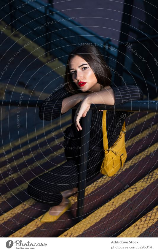 Woman in stylish outfit setting peaky cap right at city street woman fashionable trendy dusk shadow clothing standing young lady brunette accessory modern