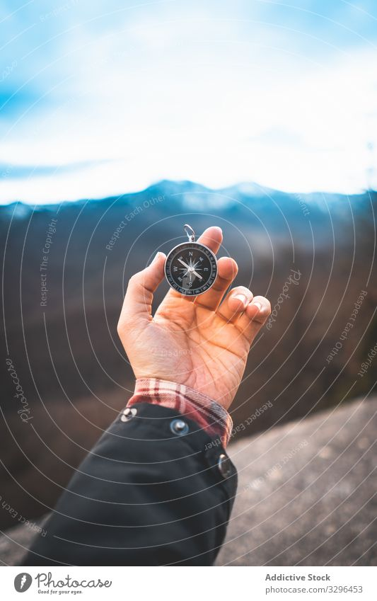 Traveler holding compass in hand in mountains traveler direction rock navigation geography orientation research sign exploration expedition tourism tool