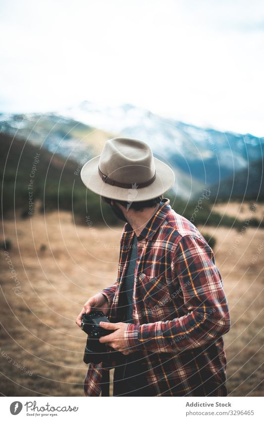 Man with camera in hand looking back at mountains traveler hat photographer nature adventure tourist vacation photography freedom wanderlust extreme