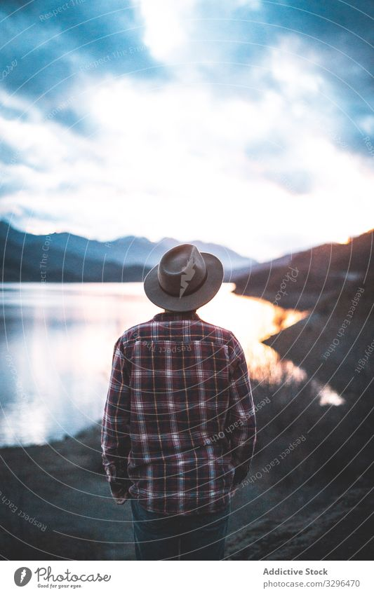 Man looking at lake reflecting clouds traveler mountain hat nature adventure tourist vacation landscape freedom wanderlust crystal extreme breathtaking holiday