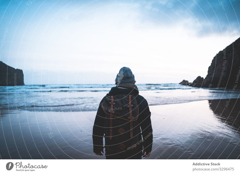 Man standing on seaside and contemplating moment traveler nature adventure mountain tourist vacation freedom wanderlust extreme breathtaking journey holiday