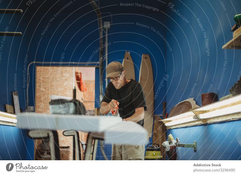 Craftsman cutting out surf board create artisan work saw small business plank workshop professional occupation craftsman handyman adult construction handmade