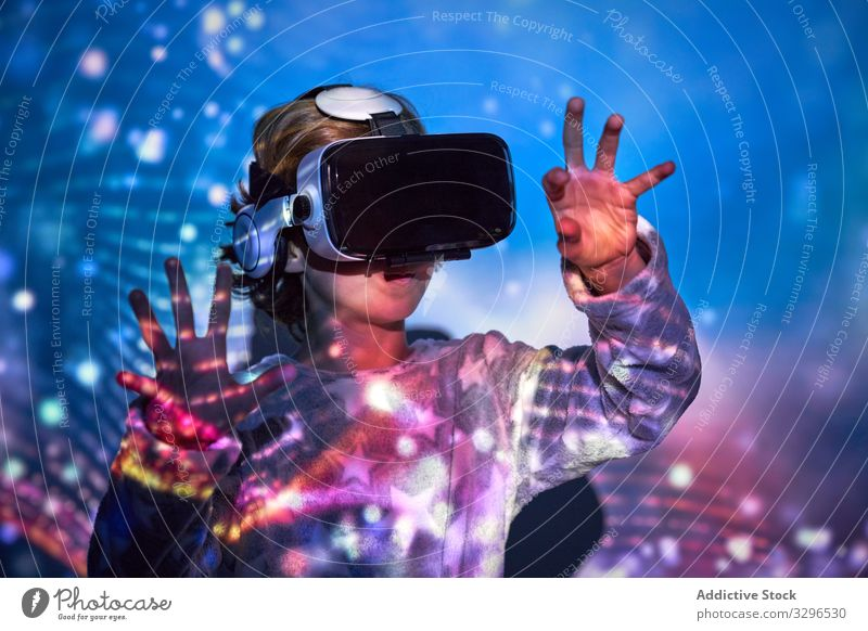 Child wearing virtual glasses at home with colored light effects child technology reality leisure childhood entertainment female headset girl adorable knowledge