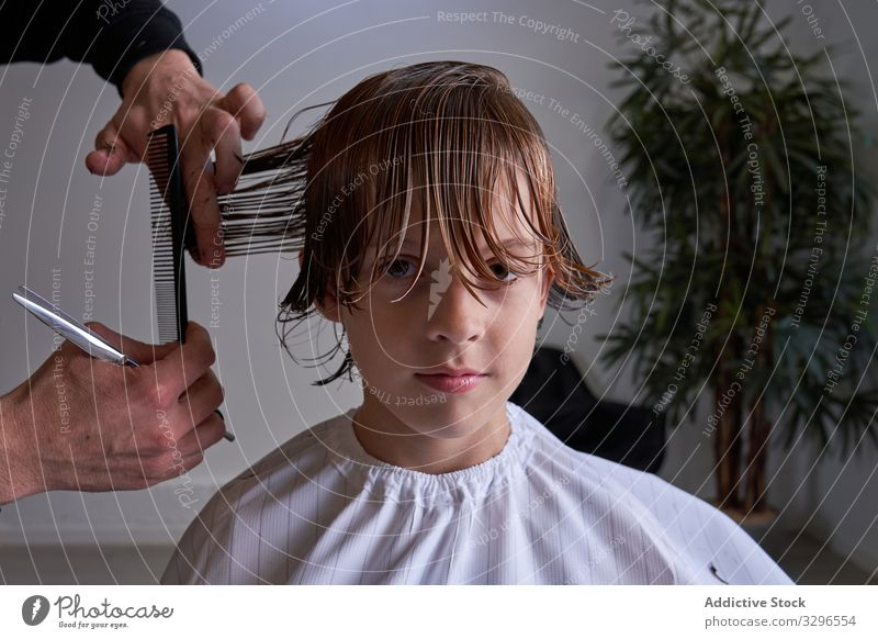 Boy cutting his hair at a hairdresser's barber barbershop child young kid fashion salon hairstyle trimming boy female haircut sitting beauty popular chair