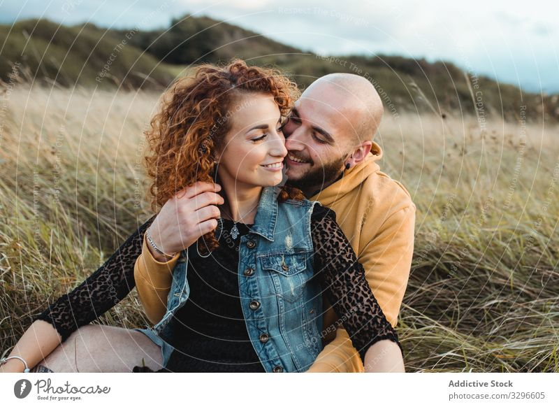 Hipster couple in love sitting in field and enjoying romantic moments embrace nature happy young together grass hug cuddle romance relationship tenderness