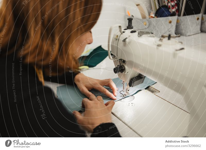 Seamstress using sewing machine in workshop seamstress woman fabric craft occupation material clothing female adult tailor part element detail professional