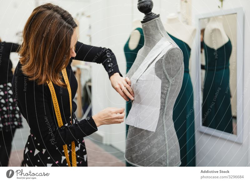 Dressmaker working with mannequin in studio dressmaker workshop woman attach cutout pin clothing designer fashion female tailor occupation craft textile clothes
