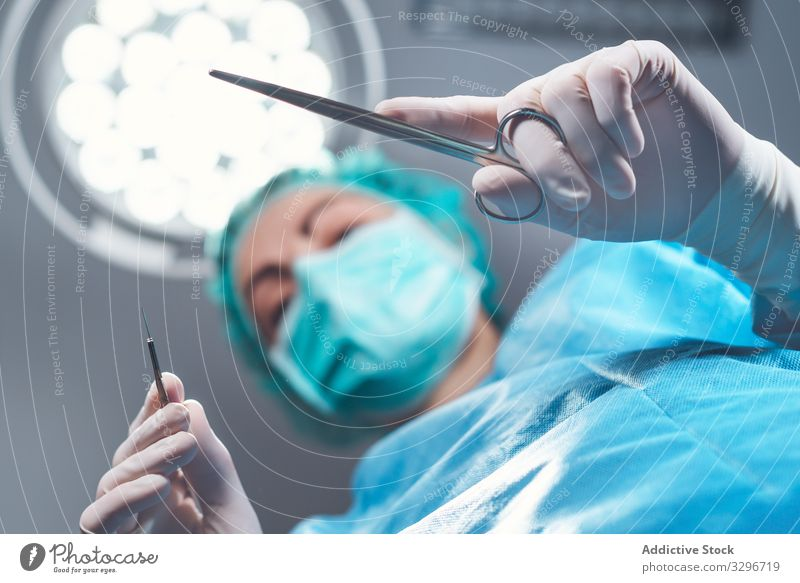 Woman performing surgery in hospital surgeon operating theater lamp tool mask hat woman work doctor healthcare female sterile instrument job uniform medicine