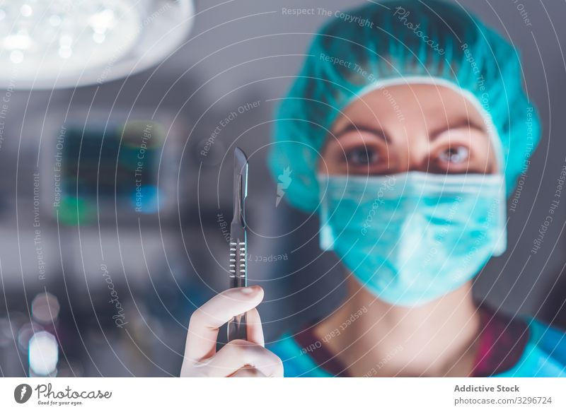 Female surgeon in operating theater hospital scalpel mask hat ready woman work doctor healthcare female sharp lancet sterile knife tool instrument job uniform