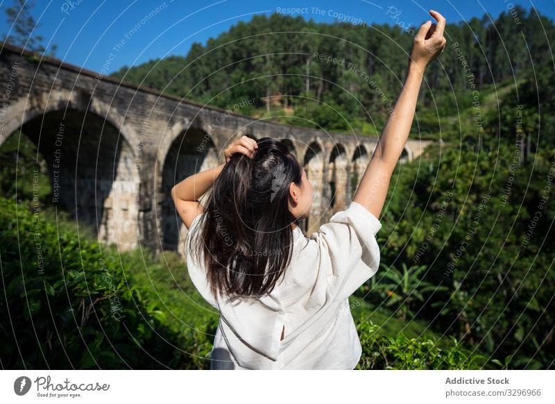 Young woman touching hair and enjoying landscape of ancient bridge green forest old asian nine arches bridge shabby ella sri lanka touristic travel