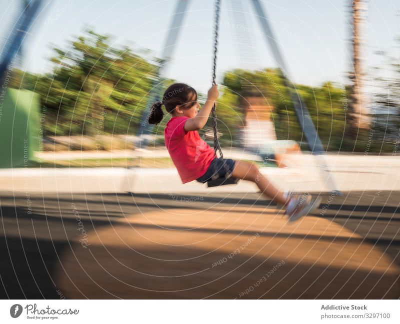 Girl on swing in park girl fun playground sunny daytime weekend summer season kid child casual activity childhood playful joy lifestyle rest relax motion