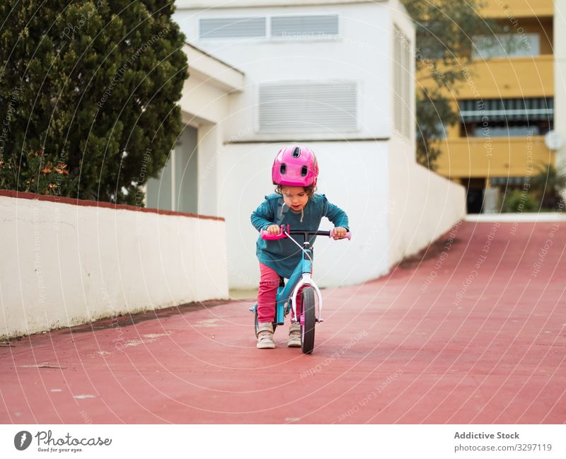 Little girl riding bicycles child ride yard street city roller skates safety protection helmet path building exterior summer season lifestyle rest relax kid