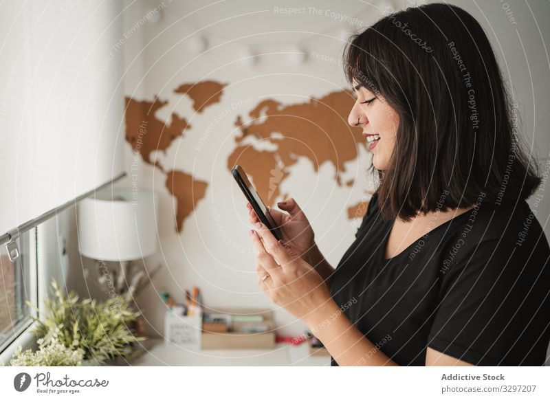 focused woman with dark hair messaging on cellphone while being near desktop computer in office in Paris employee using smartphone workplace communication