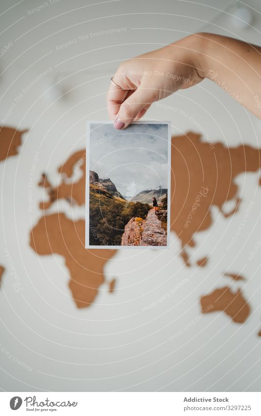 Anonymous woman holding picture in front of world map postcard photo global image information female travel lifestyle journey planet earth object geography