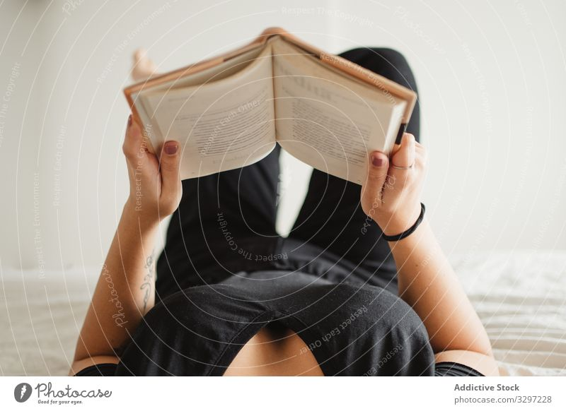 Unrecognizable woman reading book on bed at home enjoy pastime lay novel literature comfortable education female relaxation peaceful knowledge study rest cozy