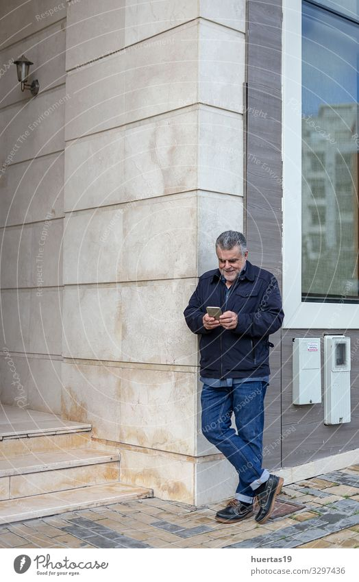 Senior man with a beard walking in the city Lifestyle Style Happy Telephone Cellphone PDA Technology Human being Masculine Man Adults Senior citizen 1