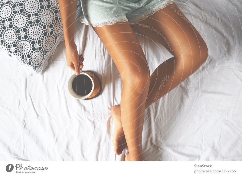 Young woman enjoying her coffee while sitting in bed. Coffee Lifestyle Joy Beautiful Relaxation Leisure and hobbies Bedroom Woman Adults Body Hand Legs 1