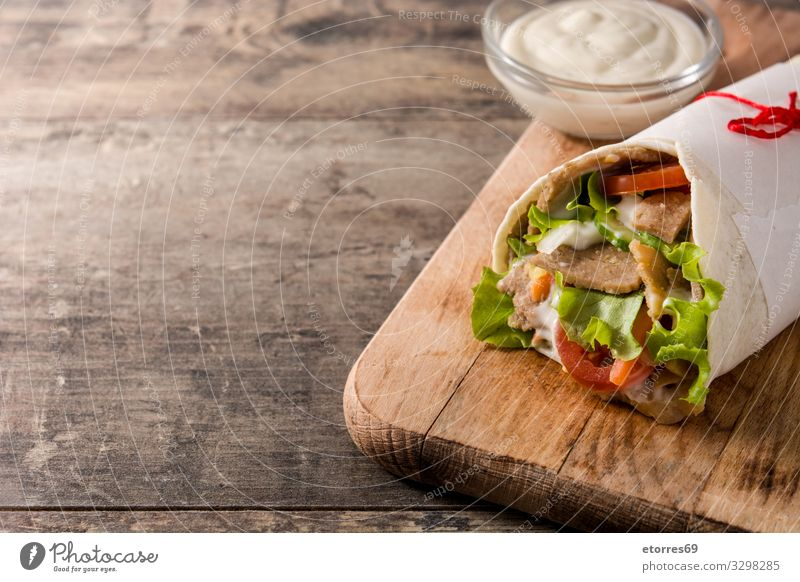 Doner kebab or shawarma sandwich on wooden table. doner Kebab Sandwich Wrap Meat Roll Chicken Vegetable Tomato Lettuce Onion Herbs and spices Sauce Greek gyros