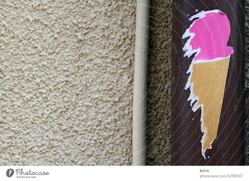 Funny, homemade sticker in the form of ice cream with ice cream ball in pink and ice cream waffle, sticks artfully, as a sticker made of paper, on a rain gutter on beige stone wall, in the city and invites you to eat ice cream.