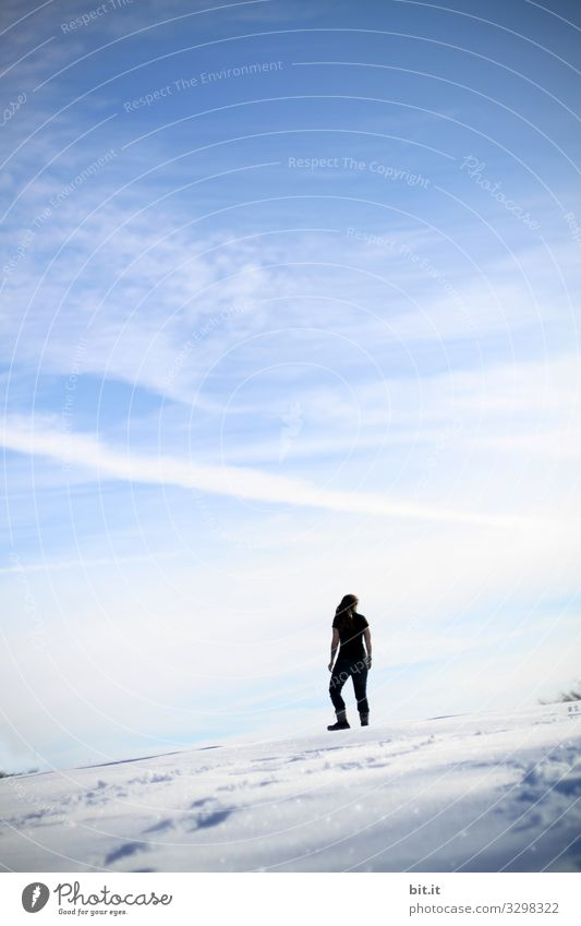 Sporty young woman in black clothing stands sleeveless, on a mountain in the snow in winter and looks up at the blue sky. Rear view of a female hiker, mountaineer, who has left tracks in the snow to enjoy the view down to the valley.