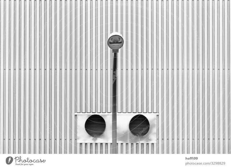 symmetrical view of a street lamp in front of two ventilation tubes with corrugated sheet metal facade Industrial plant Manmade structures Building