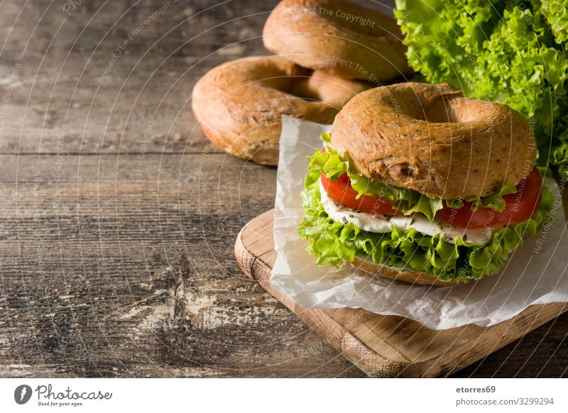 Vegetable bagel sandwich on wooden table Bagel Sandwich Food Healthy Eating Food photograph Meal Tomato Mozzarella Lettuce Cheese Snack Vegetarian diet