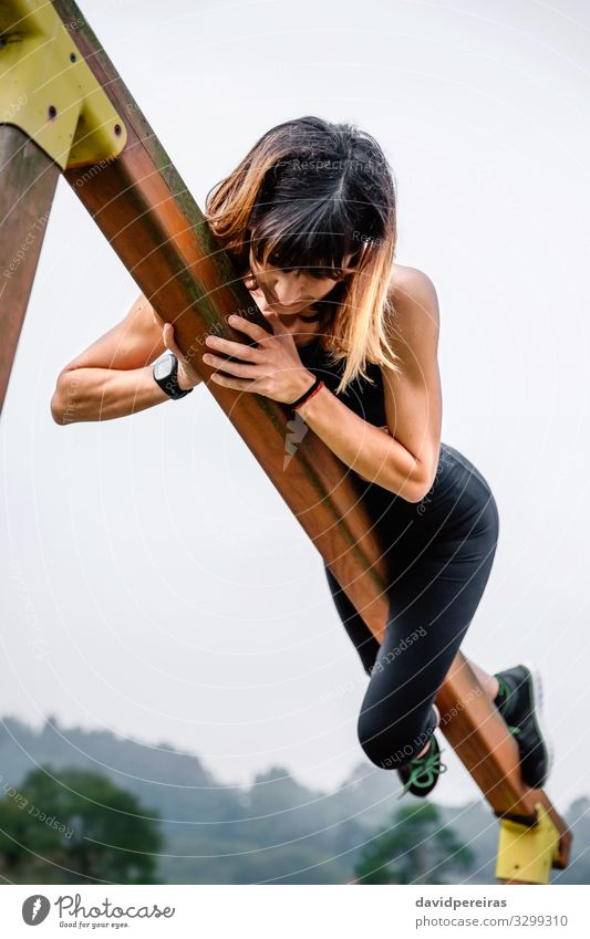 Sportswoman training grabbed to a wooden bar Lifestyle Body Climbing Mountaineering Human being Woman Adults Nature Park Fitness Thin Muscular Strong Power