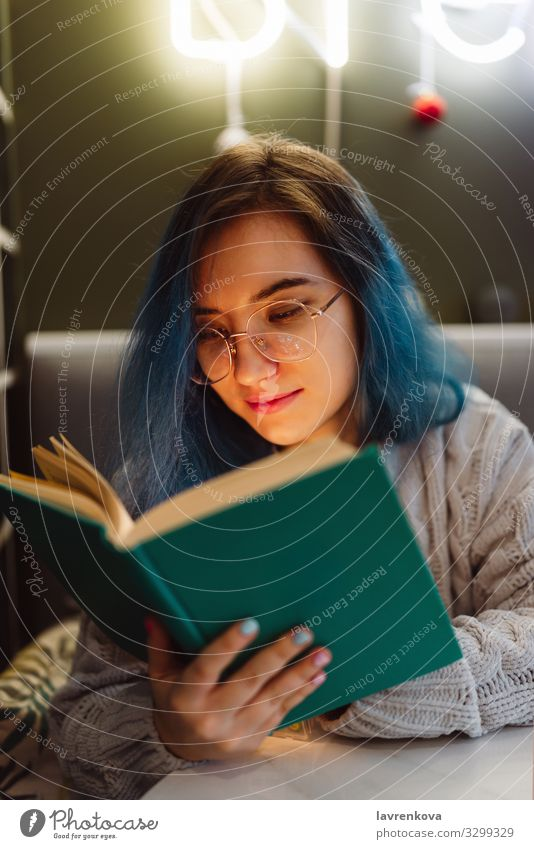 Young adult mixed asian female with blue hair holding a book in a cafe with neon lights, selective focus Beauty Photography Book Café colorful hair Face Woman