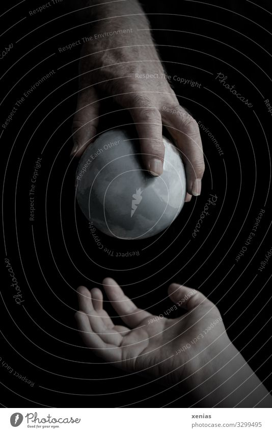 mature hand hands over grey globe to young hand Hand Fingers Environment Earth Climate Climate change Gray Black Responsibility Fear of the future