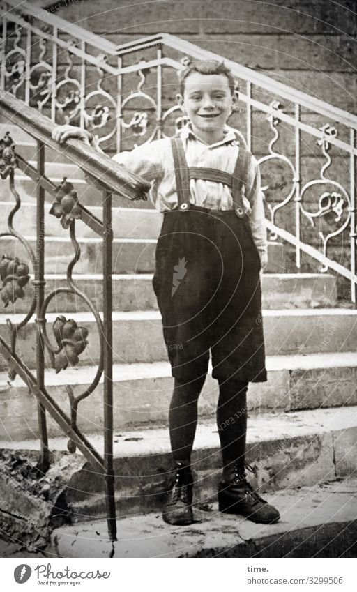 shy Masculine Boy (child) 1 Human being Wall (barrier) Wall (building) Stairs Steps Banister Shirt Pants Suspenders Boots Short-haired Observe To hold on smile