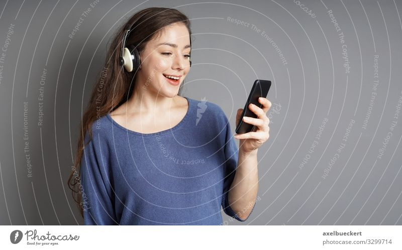 young woman streams music from smartphone via headphones Lifestyle Joy Leisure and hobbies Entertainment Music Cellphone MP3 player PDA Human being Feminine
