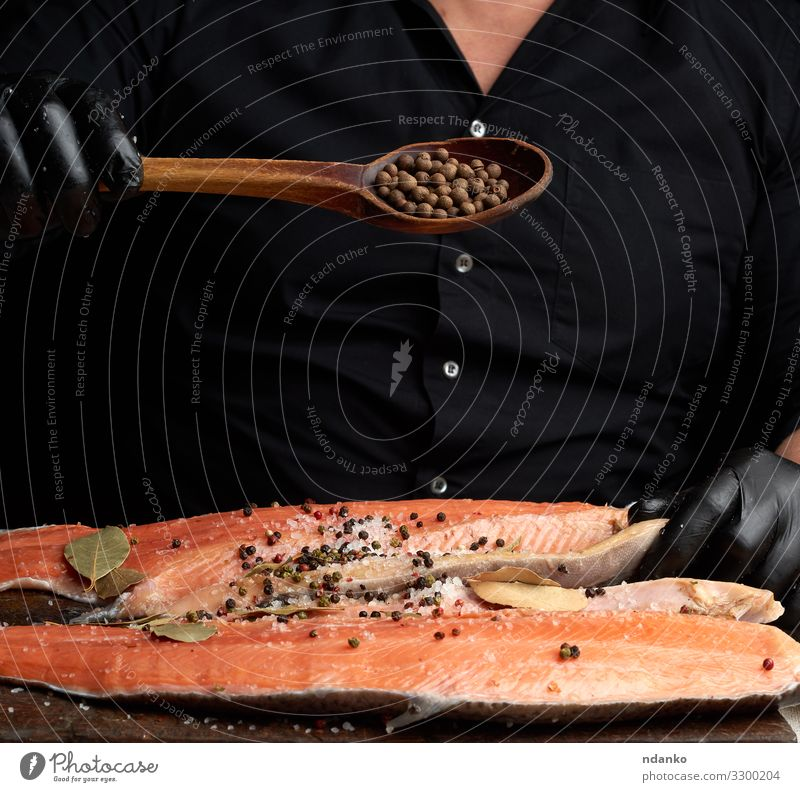 carcass of fresh salmon fish Meat Fish Seafood Herbs and spices Nutrition Dinner Spoon Table Kitchen Man Adults Gloves Wood Fresh Red Black chef cook cooking