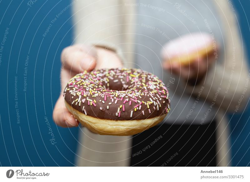 Woman holding a delicious colorful donut sprinkles Dessert Breakfast Diet Skin Adults Hand Fingers Delicious Yellow Pink Black White Donut sweet Snack isolated