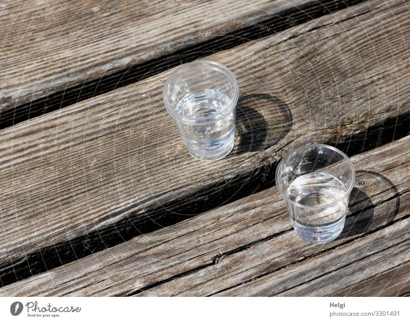 two plastic cups with liquor stand on a wooden table Beverage Alcoholic drinks Spirits Glass Wood Stand Drinking Wait Authentic Simple Small Delicious Brown