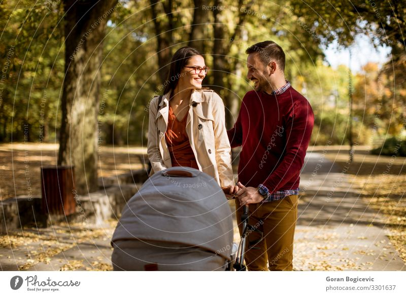Happy young parents walking in the park Lifestyle Leisure and hobbies Child Human being Baby Woman Adults Man Mother Father Family & Relations Couple Partner