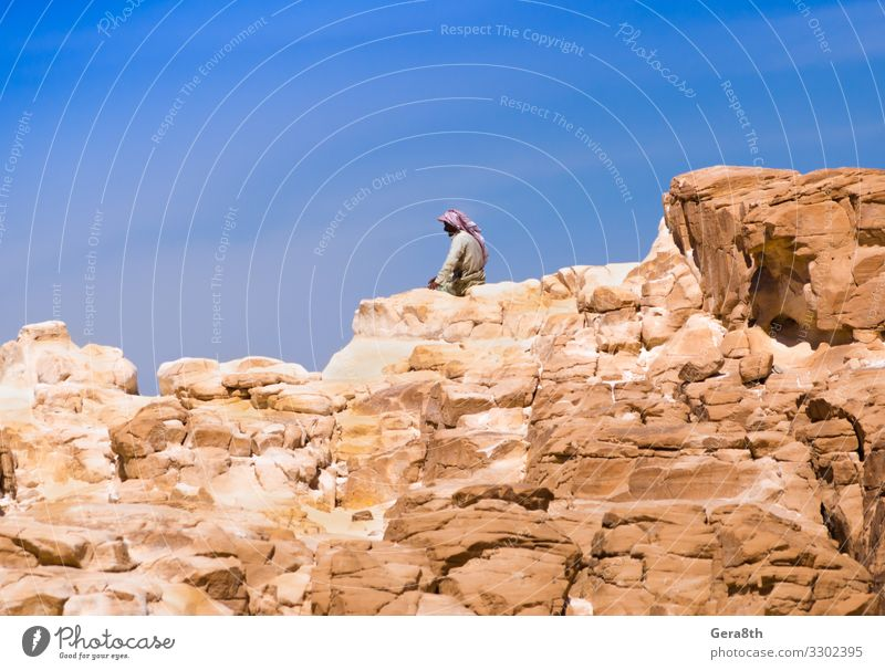 Bedouin sitting on the peak of a high rock in Egypt Relaxation Calm Vacation & Travel Summer Mountain Human being Man Adults Nature Landscape Sky Clouds Rock
