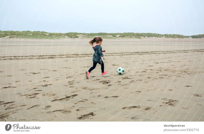 Girl playing soccer on the beach Lifestyle Joy Leisure and hobbies Playing Beach Sports Child Human being Woman Adults Infancy Nature Plant Sand Sky Autumn Fog