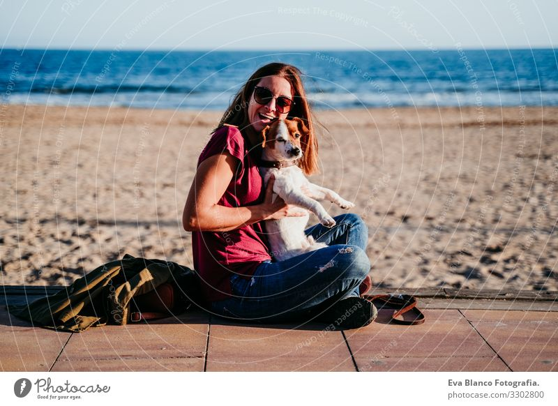 happy woman and her cute cute sitting at the beach Woman Dog Jack Russell terrier Love Beach Sunset Together White Leisure and hobbies Beautiful Lifestyle