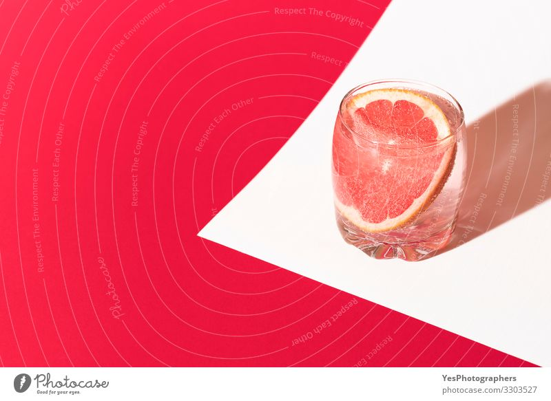 Cold grapefruit drink. Pink beverage. Grapefruit water. Cocktail Cold drink Drinking water Lemonade Glass Wellness Fresh Red citrus colorful Copy Space