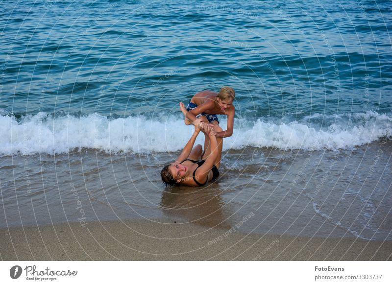 Two funny children play together on a beach in front of a sea wave two Brothers and sisters brother and sister Beach Sandy beach Ocean people Fight Funny Joy