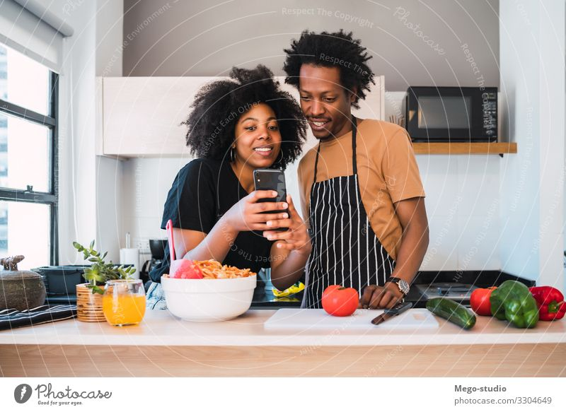Afro couple cooking together and using phone at home. Lifestyle Happy Leisure and hobbies Flat (apartment) House (Residential Structure) Kitchen Telephone