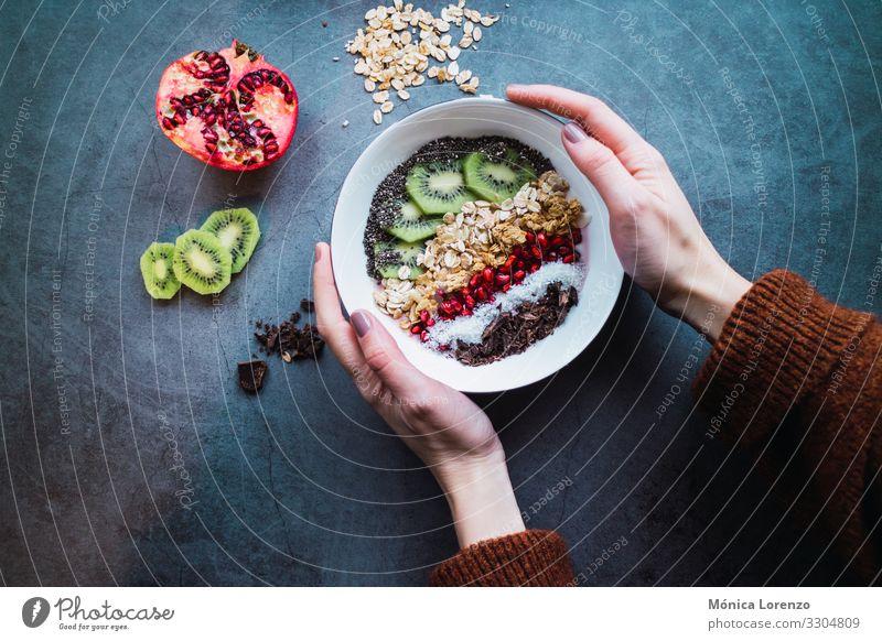 Woman's hands holding a smoothie bowl with vegan ingredients. Yoghurt Fruit Dessert Breakfast Vegetarian diet Diet Bowl Human being Adults Hand Concrete