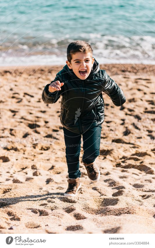 Little kid running on the beach in a winter day Lifestyle Joy Happy Beautiful Leisure and hobbies Playing Vacation & Travel Freedom Beach Ocean Winter Child