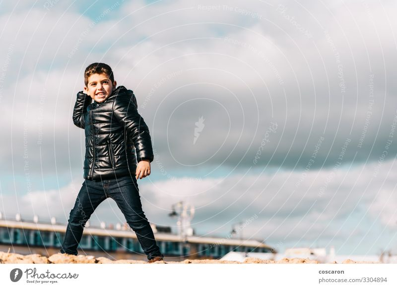 Cute kid throwing rocks with cloudy sky background Lifestyle Joy Happy Leisure and hobbies Playing Vacation & Travel Adventure Beach Ocean Winter Sports Child