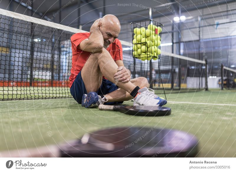 senior man playing paddle tennis in court Playing Sports Man Adults Bald or shaved head Beard Old Sit Fatigue Pain Competition padel Court building match